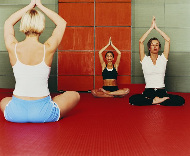 Three Women Sit Cross-legged on the Floor of a Gym With Their Arms Raised for a Yoga Exercise