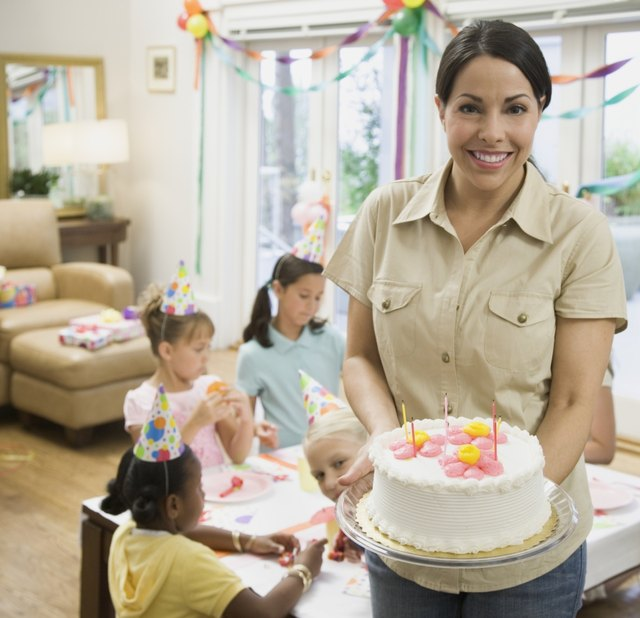 Hispanic mother holding cake at daughter's birthday party