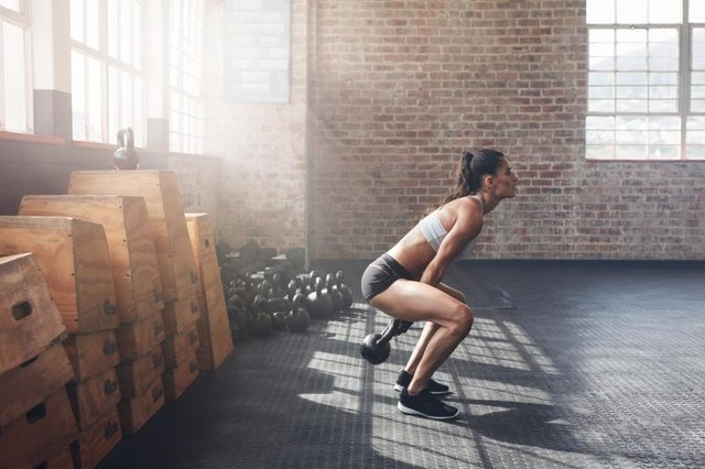 Side view of tough young woman exercising with kettle bell at gym. Fit female athlete doing gym workout at gym.