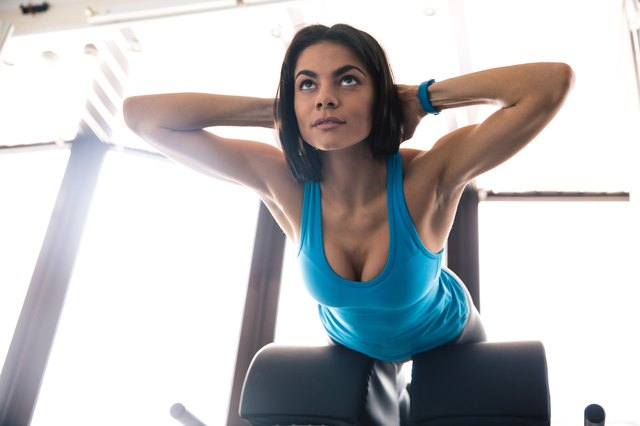 young woman flexing back muscles on bench