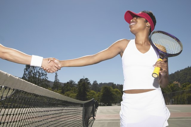 Young woman shaking hands with a man over a tennis net