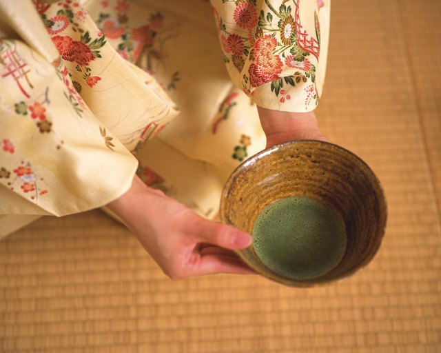 Woman in kimono holding a cup of green tea, close up