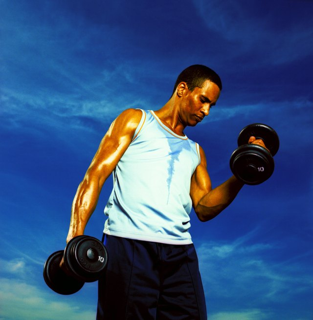 Low angle view of a young man exercising with dumbbells