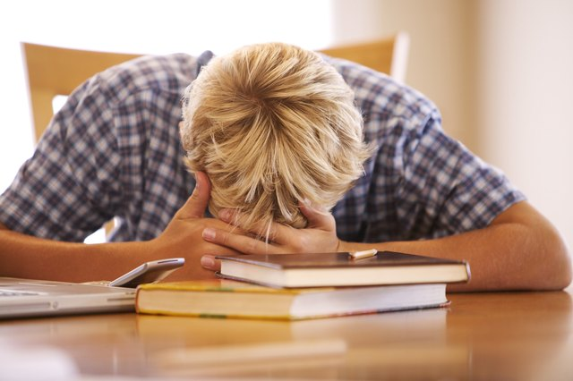 A boy lies his head down on the table while doing homework