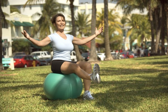 Woman balancing on exercise ball in park