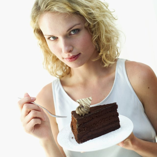 Portrait of a young woman holding a piece of chocolate cake on a plate