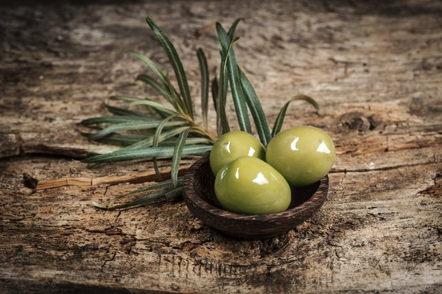Olives with leaves on a wooden surface.