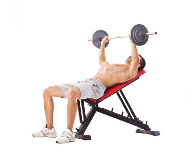 Handsome man doing incline bench press. Studio shot, isolated on white.