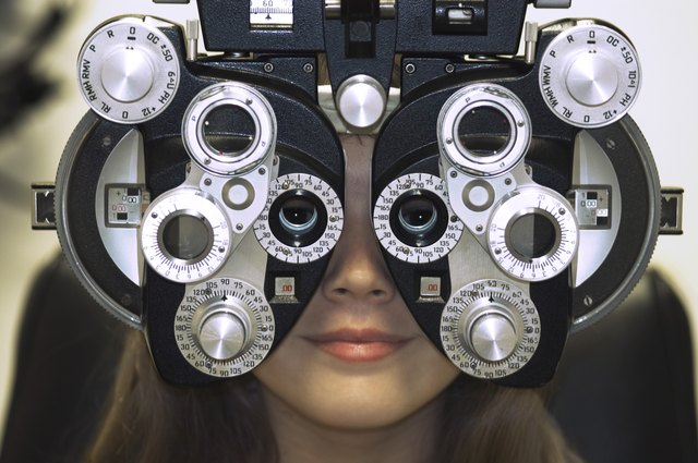 Close-up of a young woman getting an eye test with a phoropter