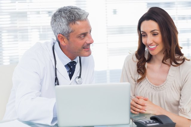 Docter showing something on laptop to his patient