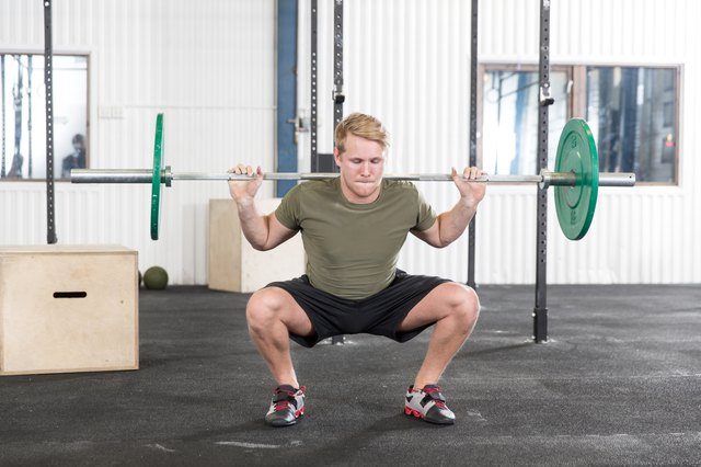 Squats training at fitness gym center