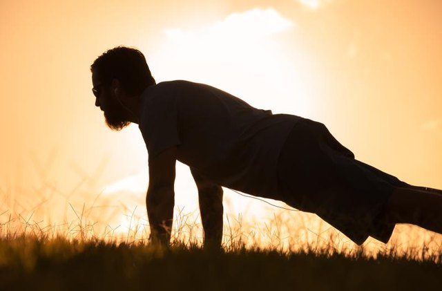 Silhouette of male doing push ups in the park.