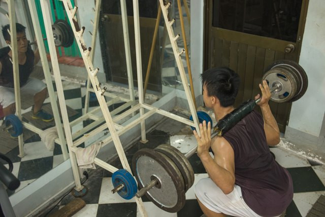 Muscular man weightlifting, exercising very hard in the gym