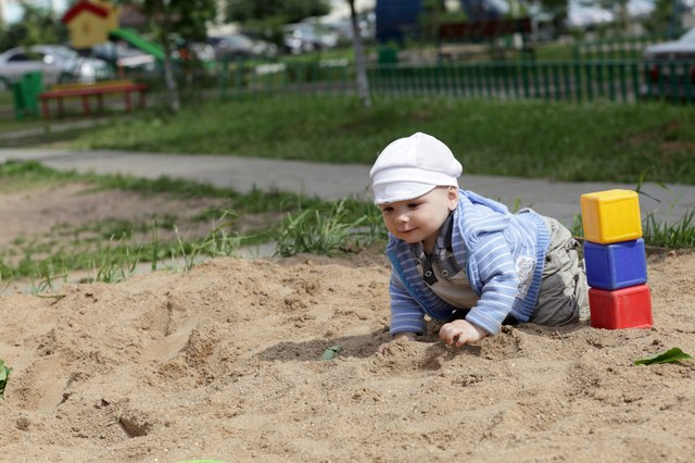 Child creeping in sandbox