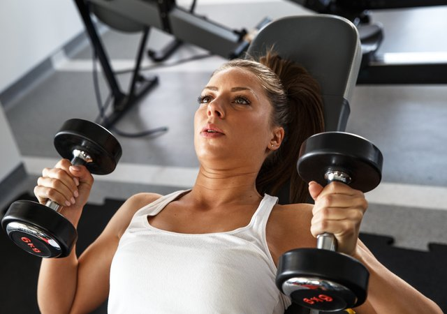 Woman lifting weights at the the gym