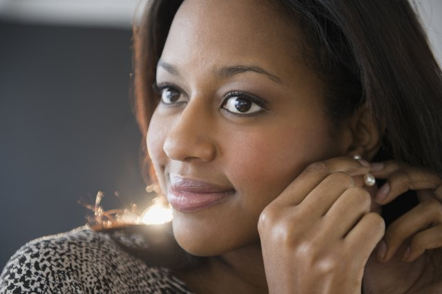 African American woman putting on earrings