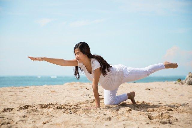 Pregnant asian woman doing yoga in the sea shore
