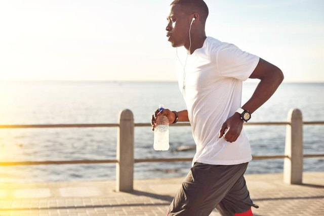 Young black male jogging next to the ocean.
