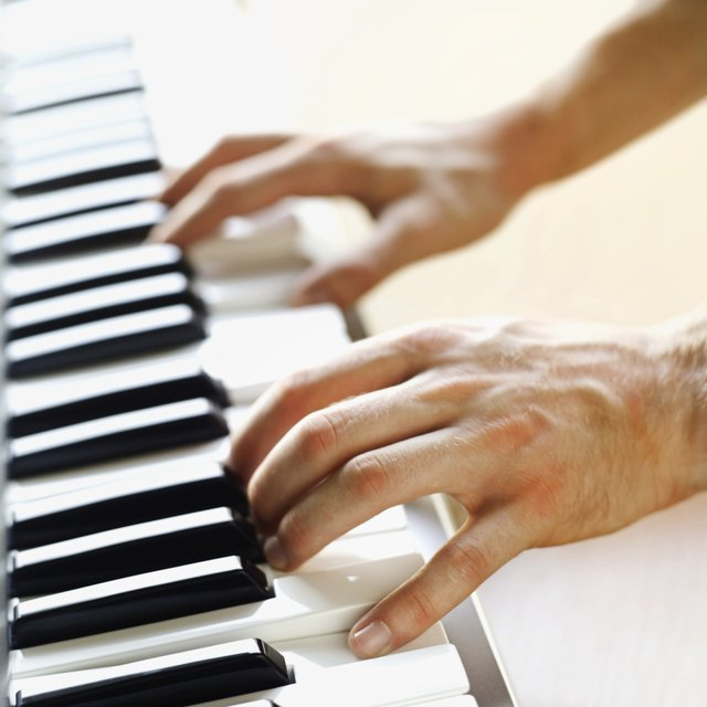Man playing a keyboard close-up of hands
