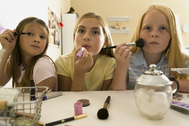 teenage lifestyle shot of three female friends as they sit at a vanity and put on make up