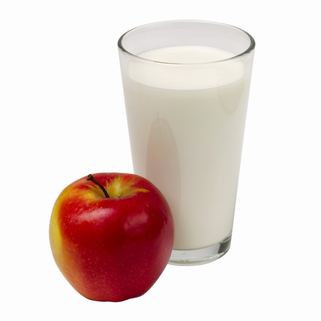 Close up of a glass of milk and an apple