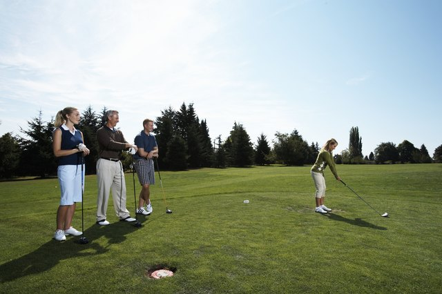 Group of golfers watching female golfer tee off