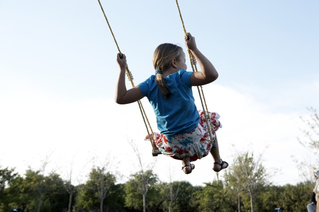 Young girl (8-9) swinging outdoors, rear view