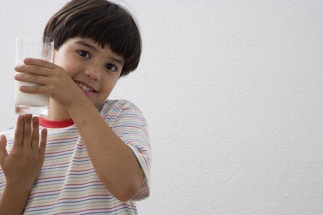 Boy (8-9) holding glass of milk, portrait