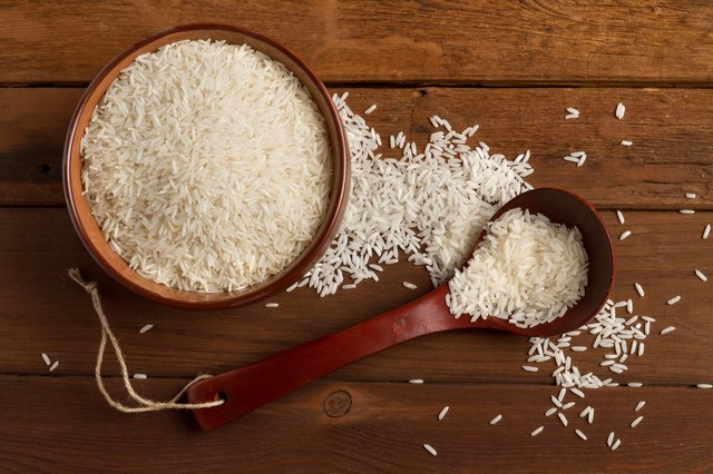 Rice in ceramic bowl and spoon on a wooden table