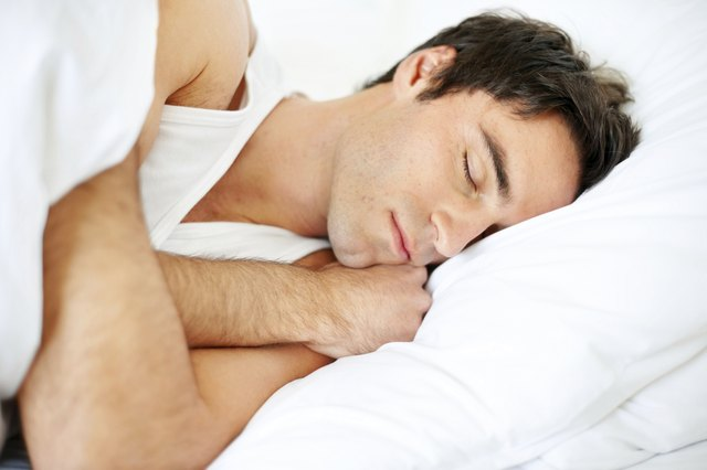 Handsome young guy sleeping in bed