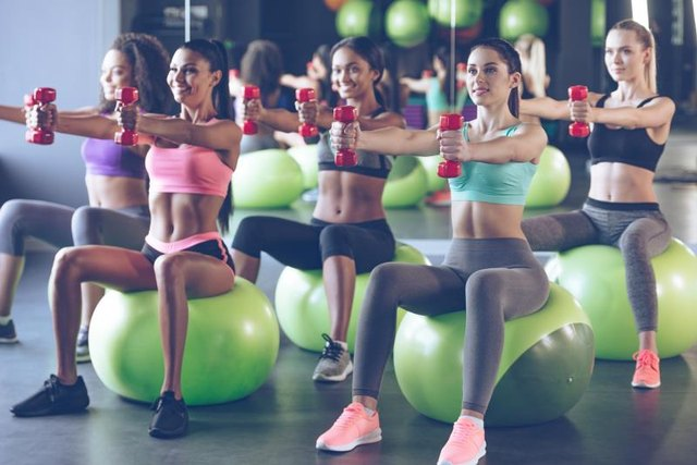 Young beautiful women in sportswear with perfect bodies exercising with dumbbells while sitting on fitness balls at gym