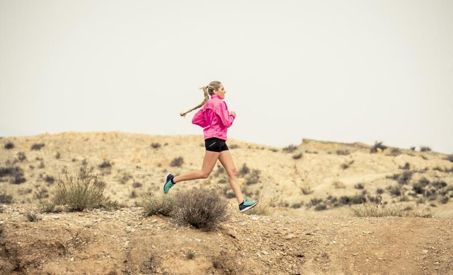 young attractive sport woman running on off road trail dirty road with dry desert landscape background training hard in jogging training workout , healthy  fitness and wellness concept