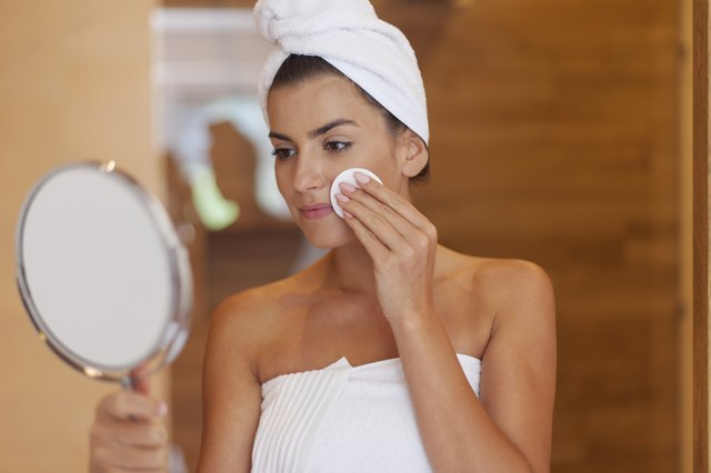 Woman cleaning face in bathroom