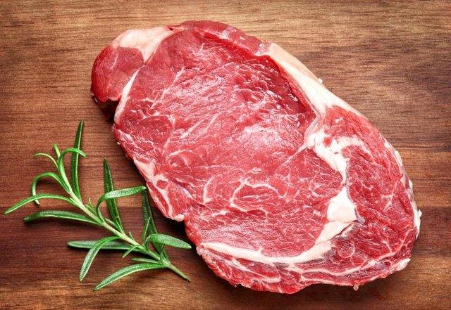 raw beef steak on wooden cutting board