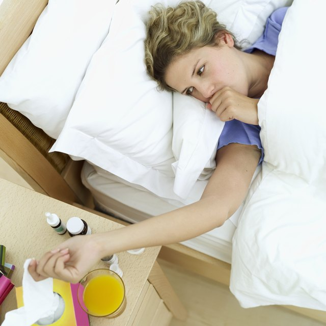 woman lying in a bed reaching for a tissue on the bed side table
