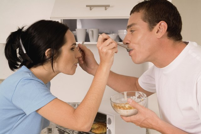 Couple feeding each other cereal in kitchen, close-up