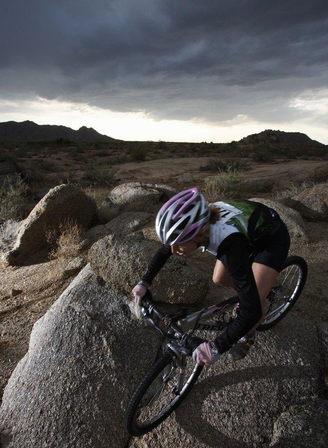 Female rider mountain biking between rocks, elevated view