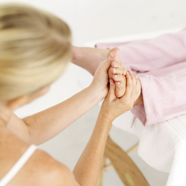 high angle view of a masseuse massaging a persons foot