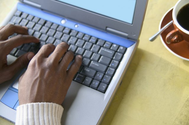 High angle view of young man operating a laptop