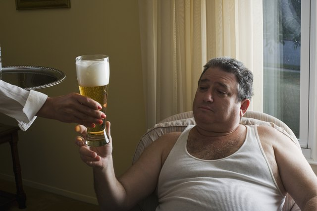 Mature overweight man sitting in armchair, maid (close-up of hand) serving glass of beer