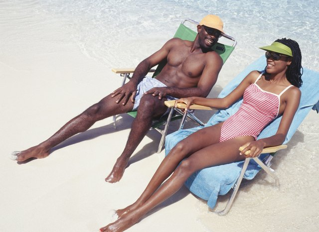 Man and woman sunbathing in deckchairs on beach, elevated view