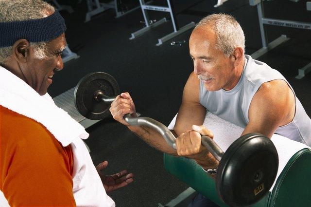 Senior man helping mature man weight train in gym