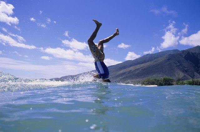 Man standing on head on surfboard at ocean