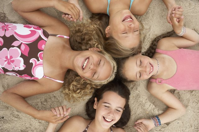 Four girls (8-12) lying in circle on beach, holding hands, eyes closed