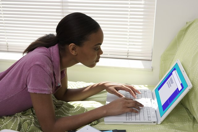 Young woman lying on bed uisng laptop computer, in student dormitory