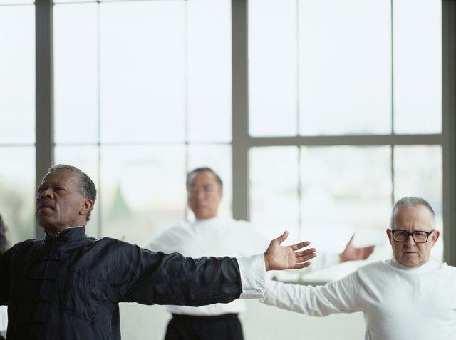 Three men exercising in gymnasium