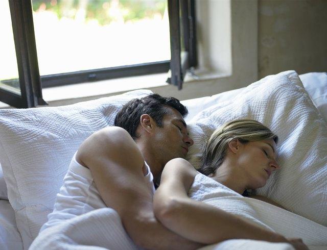 Couple sleeping in bed under open window