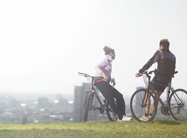 Man and woman talking while resting on hill after bike ride