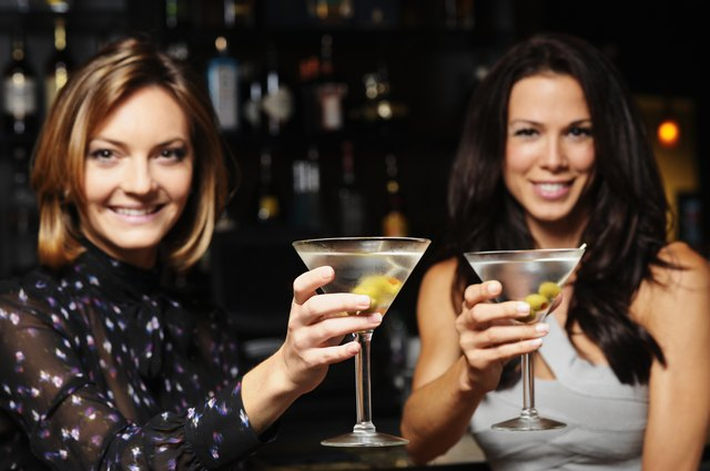 Two Young Women Toasting Drinking Martinis in Bar