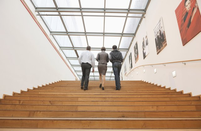 Three business people going upstairs